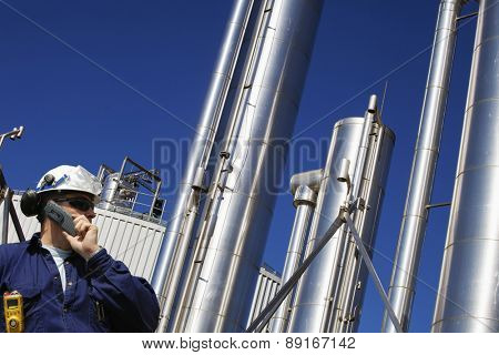 oil and gas engineer with large gas-pipes pipelines in the background