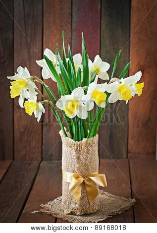 Bouquet of yellow narcissuses close up on a rustic wooden background