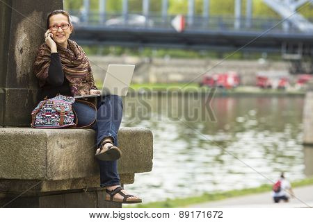 Young woman sitting with laptop on the waterfront of the old town and talking on the phone. Freelancer.
