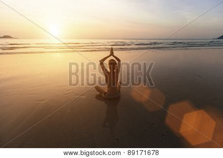 Beautiful girl sitting on the beach during sunset and meditating in yoga pose.