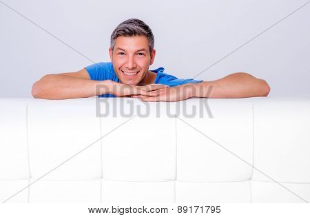friendly male looking over white couch