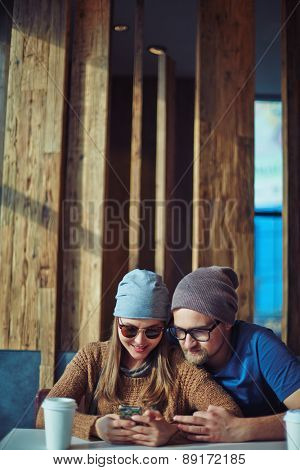 Modern couple with smartphone having rest in cafe