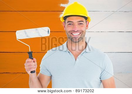 Portrait of manual worker holding paint roller against painted blue wooden planks