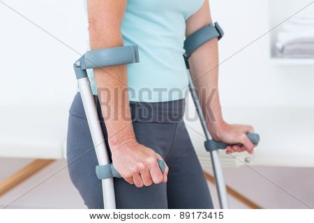 Woman standing with crutch in medical office