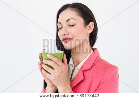 Smiling brunette smelling her coffee on white background