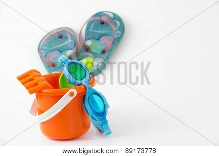 summer toys bucket with spade goggles flip flops isolated on white background