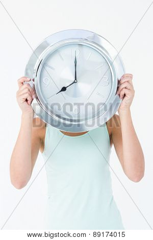 Woman holding clock in front of her head on white background