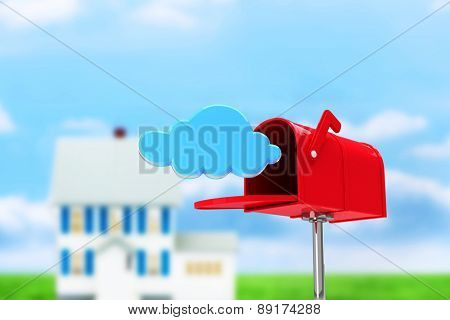 Red email postbox against house in the distance