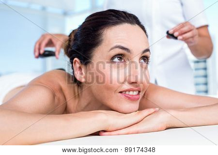 Smiling brunette getting hot stone massage in a healthy spa
