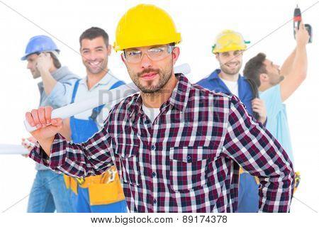 Composite image of handyman holding rolled up blueprint