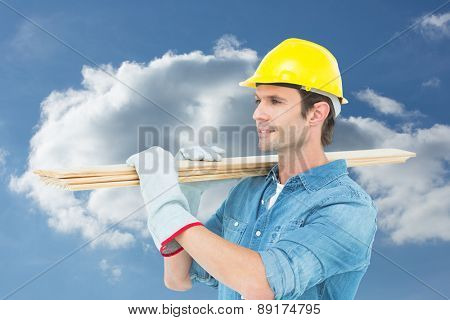 Carpenter carrying wooden planks over white background against cloudy sky