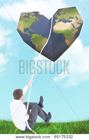 Businessman pulling a rope with effort against blue sky