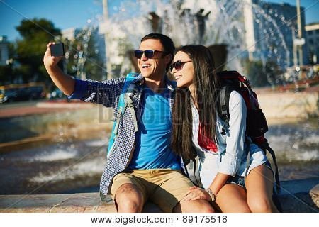 Affectionate couple with rucksacks making selfie on background of fountain