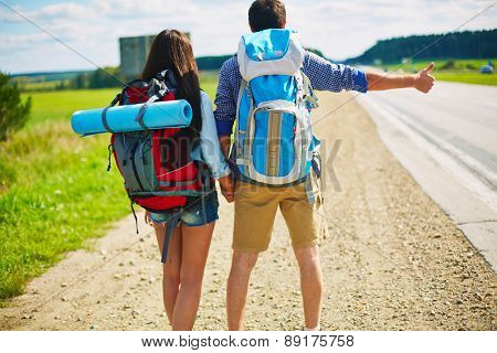 Young man and woman with rucksacks hitch-hiking by road