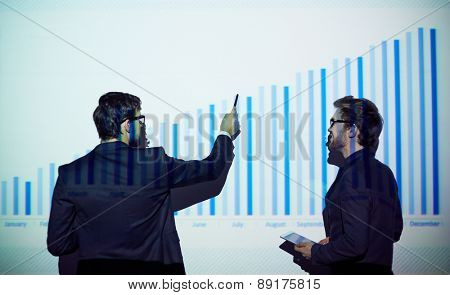 Young businessman with touchpad listening to his colleague explaining chart on the wall