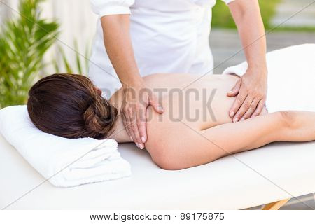 Brunette having back massage in the health spa