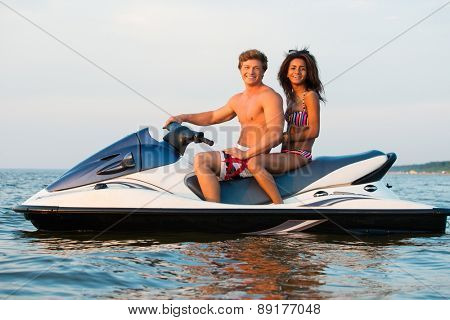 Multinational couple sitting on a jet ski