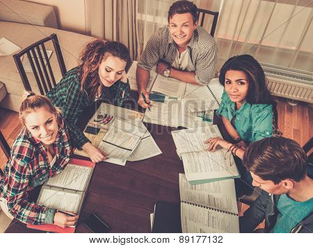 Multi ethnic group of students preparing for exams in home interior behind table
