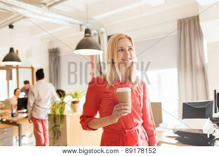 business, startup and people concept - happy businesswoman or creative female office worker with coffee cup