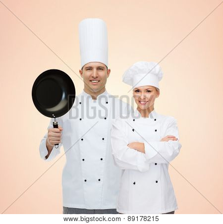 cooking, profession, teamwork, kitchenware and people concept - happy chefs or cooks couple with frying pan over beige background