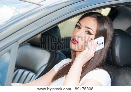 Young beautiful girl talking on the phone while driving