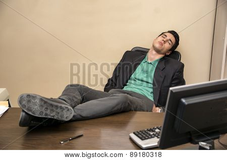 Overworked, tired young businessman sleeping at his desk