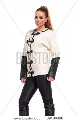 Side view of a young fashion woman wearing a white jacket and leather pants.