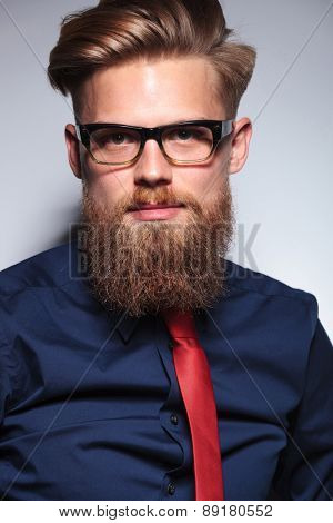 Close up picture of a long beard business man on grey studio background.