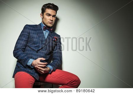 Handsome young fashion man looking away from the camera while sitting on a chair.