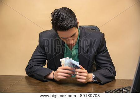 Sitting Young Businessman Counting Cash on Hand