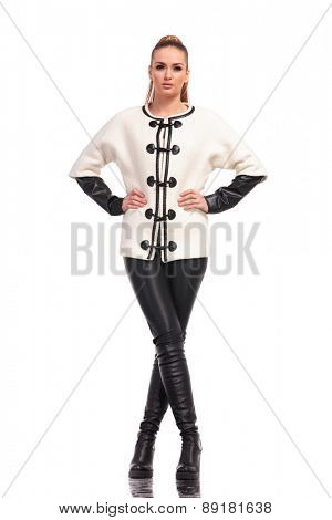 Beautiful young attractive fashion woman standing with her legs crossed on isolated background.
