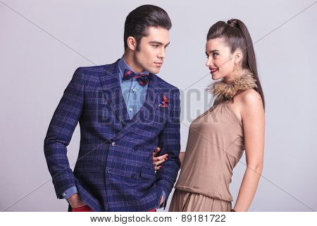 Handsome young fashion man looking at his lover while she is holding his arm.
