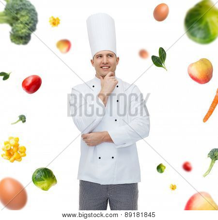 cooking, profession, inspiration, vegetarian diet and people concept - happy male chef cook thinking over falling vegetables background