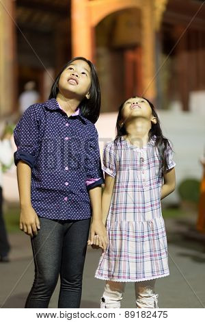 CHIANG MAI, THAILAND, JANUARY 01, 2015: Two little girls are looking up a Buddhist floating lantern going up for the new year evening at the Wat Phra Singh temple in Chiang Mai, Thailand