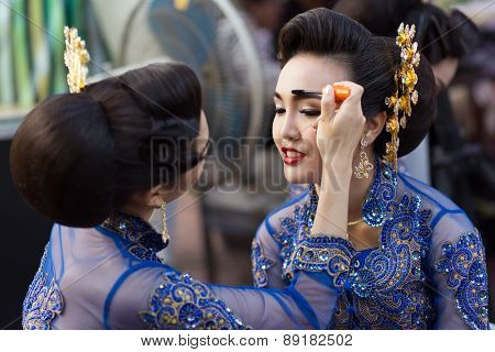 BANGKOK, THAILAND, February 17, 2015: A Thai lady dancer is applying make up on eyebrow's friend before the show in the new Krung Kasem floating market in the Thewet district of Bangkok, Thailand
