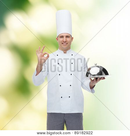 cooking, profession, gesture and people concept - happy male chef cook holding cloche and showing ok sign over green background