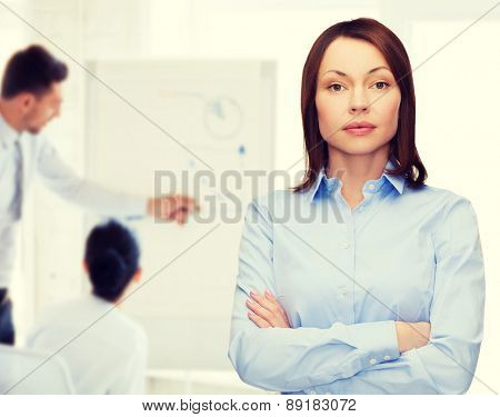 business and education concept - friendly young businesswoman with crossed arms at office
