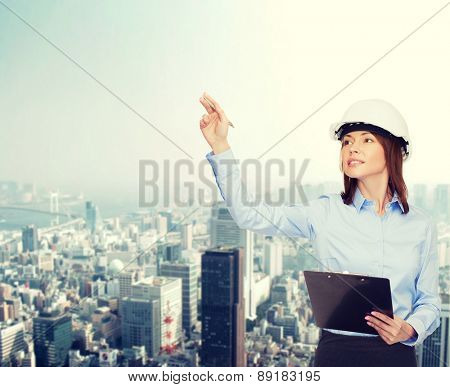 building, developing, consrtuction and architecture concept - smiling businesswoman in white helmet with clipboard pointing finger