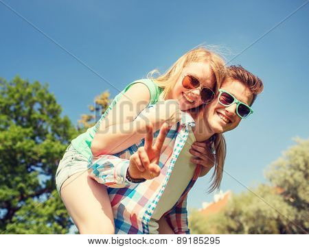 holidays, vacation, love, gesture and friendship concept - smiling couple having fun and showing peace or victory sign in park