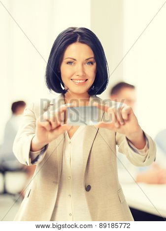 business and bank concept -  smiling businesswoman showing credit card in office