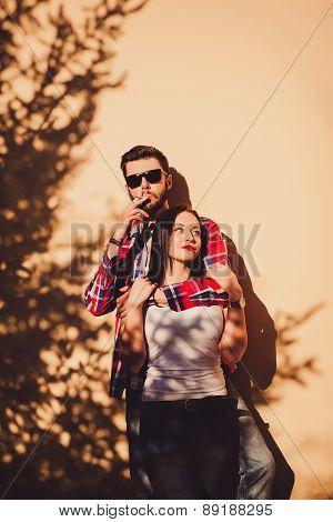 Couple Standing Near The Wall. Man Smoking