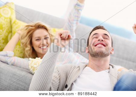 A picture of sport fans cheering at home while watching tv