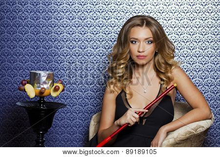 Beauty portrait of young curly blonde woman resting in the hookah room