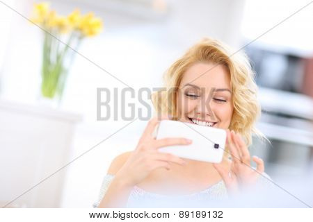 A picture of a happy woman using smart phone at home