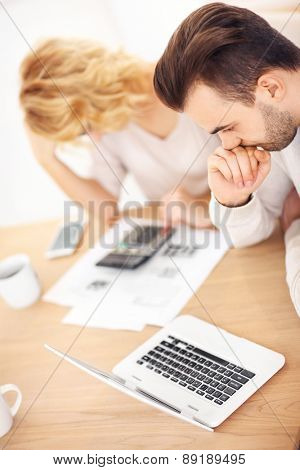 A picture of a young worried couple with documents at home