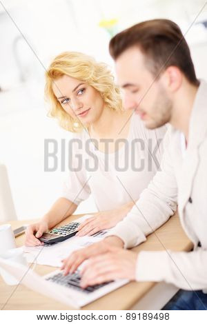 A picture of a happy couple planning home budget in the kitchen