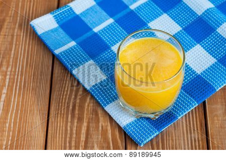 Healthy homemade orange juice in glass on wooden background.