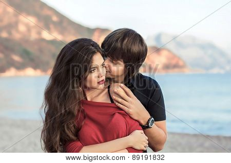 Romantic Couple In Love At Beach Sunset. Newlywed Happy Young Lovers Embracing Enjoying Honeymoon Ho