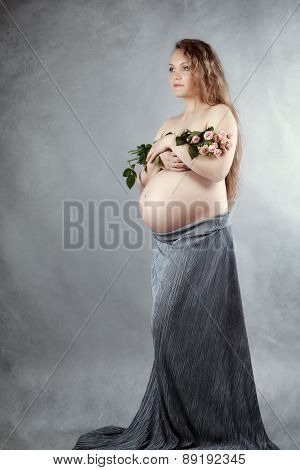 Beautiful Pregnant Woman Holding Flowers In Her Arms, Studio