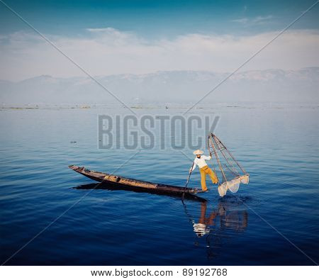 Myanmar travel attraction - Traditional Burmese fisherman with fishing net at Inle lake, Myanmar famous for their distinctive one legged rowing style. Vintage filtered retro effect hipster style image
